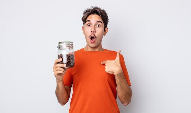 Jovem hispânico parecendo chocado e surpreso com a boca aberta, apontando para si mesmo. conceito de grãos de café