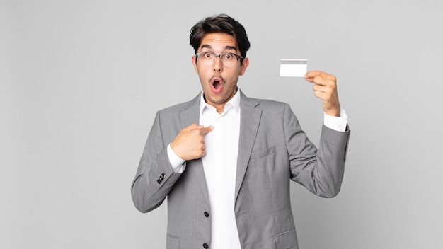 Jovem hispânico parecendo chocado e surpreso com a boca aberta, apontando para si mesmo e segurando um cartão de crédito