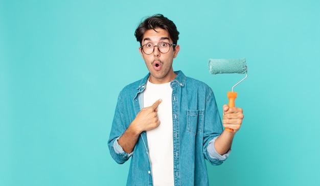 Jovem hispânico parecendo chocado e surpreso com a boca aberta, apontando para si mesmo e segurando um rolo de pintura