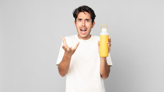Jovem hispânico parecendo desesperado, frustrado e estressado com uma garrafa térmica de café