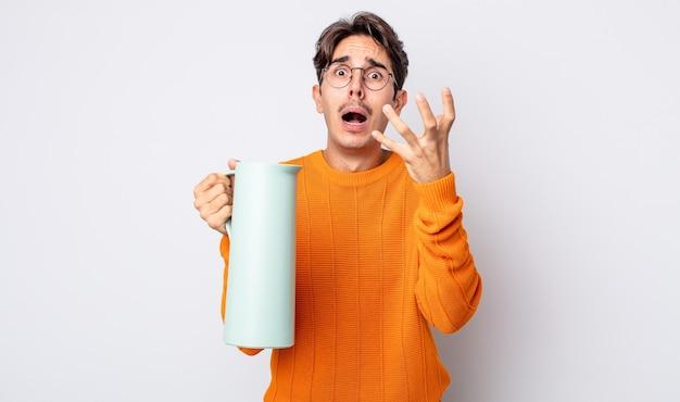Jovem hispânico parecendo desesperado, frustrado e estressado. conceito de garrafa térmica