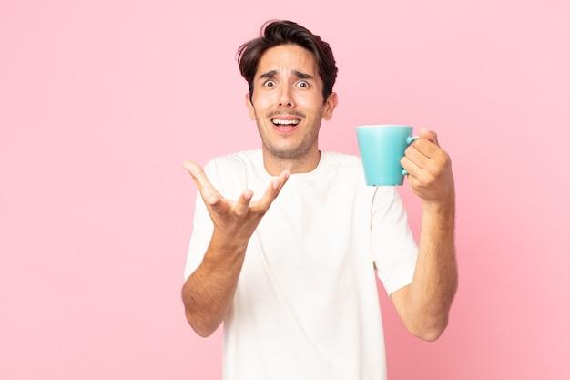 Jovem hispânico parecendo desesperado, frustrado e estressado, segurando uma caneca de café