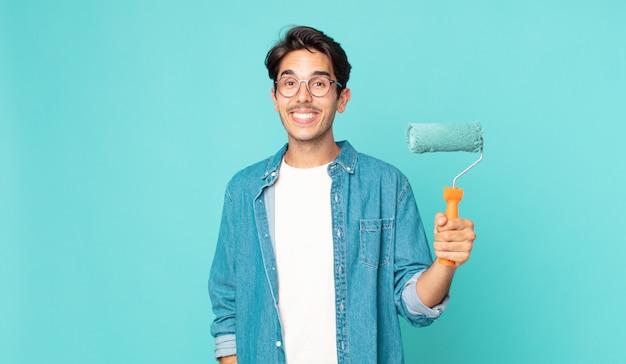 Jovem hispânico parecendo feliz e agradavelmente surpreso, segurando um rolo de pintura