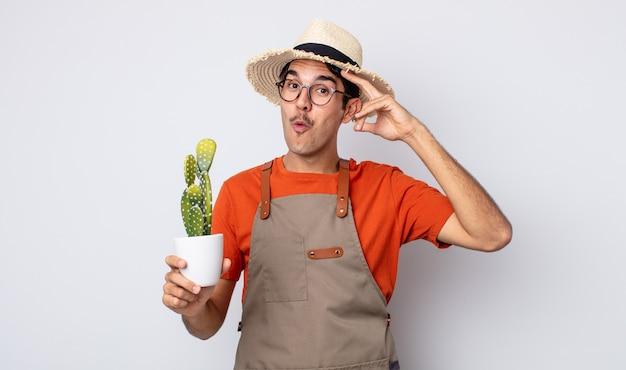 Jovem hispânico parecendo feliz, espantado e surpreso. jardineiro com conceito de cacto