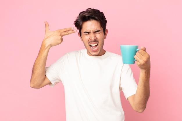 Jovem hispânico parecendo infeliz e estressado, gesto suicida fazendo sinal de arma e segurando uma caneca de café