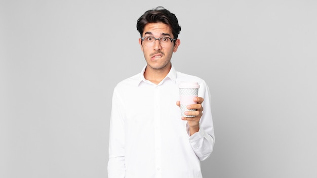 Jovem hispânico parecendo perplexo e confuso, segurando um café para viagem
