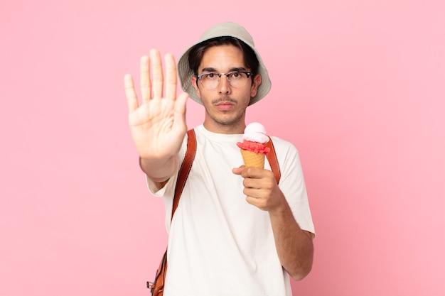 Jovem hispânico parecendo sério, mostrando a palma da mão aberta fazendo gesto de pare e segurando um sorvete