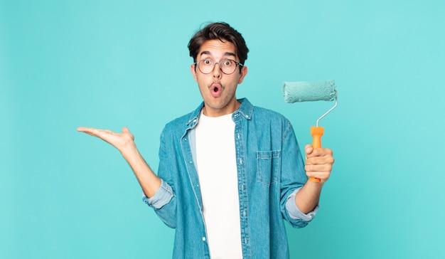 Jovem hispânico parecendo surpreso e chocado, com o queixo caído segurando um objeto e um rolo de pintura