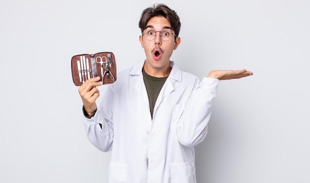 Jovem hispânico parecendo surpreso e chocado, com o queixo caído segurando um objeto. ferramentas de unhas quiropodistas
