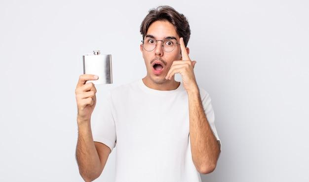 Jovem hispânico parecendo surpreso, percebendo um novo pensamento, ideia ou conceito. conceito de frasco de álcool