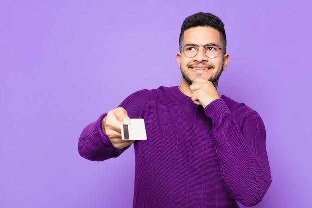 Jovem hispânico pensando em expressão e segurando um cartão de crédito