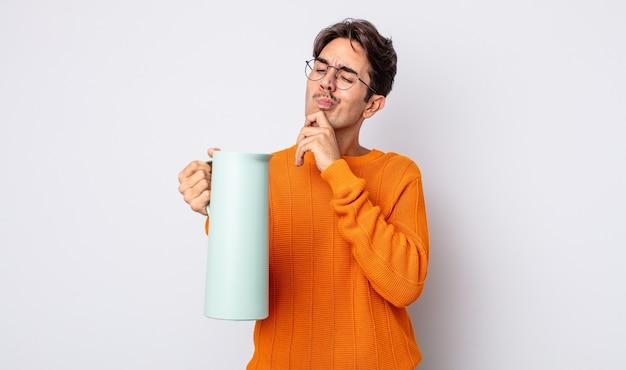 Jovem hispânico pensando, sentindo-se duvidoso e confuso. conceito de garrafa térmica