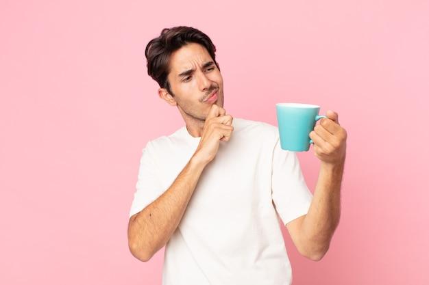 Jovem hispânico pensando, sentindo-se duvidoso e confuso e segurando uma caneca de café