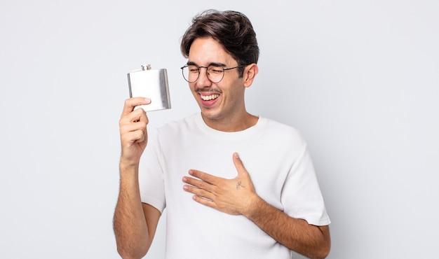 Jovem hispânico rindo alto de alguma piada hilária. conceito de frasco de álcool