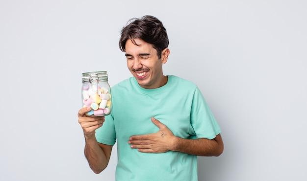 Jovem hispânico rindo alto de uma piada hilária. conceito de balas de geleia