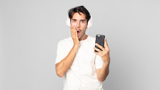 Jovem hispânico se sentindo chocado e assustado com fones de ouvido e smartphone