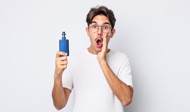 Jovem hispânico se sentindo chocado e com medo. conceito de vaporizador de fumaça