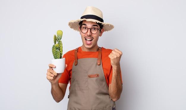 Jovem hispânico se sentindo chocado, rindo e comemorando o sucesso. jardineiro com conceito de cacto