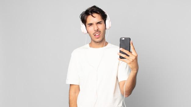 Jovem hispânico se sentindo perplexo e confuso com fones de ouvido e smartphone