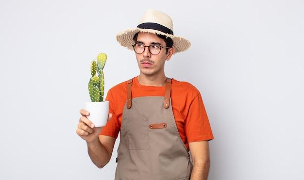Jovem hispânico se sentindo triste, chateado ou com raiva e olhando para o lado. jardineiro com conceito de cacto