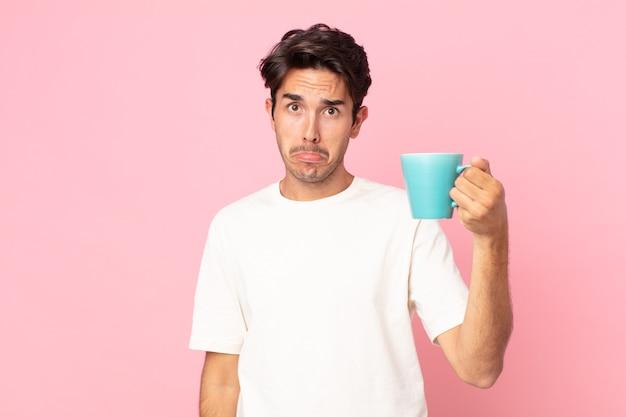Jovem hispânico se sentindo triste e choramingando, com uma aparência infeliz, chorando e segurando uma caneca de café