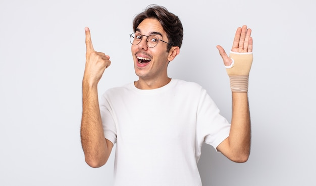 Jovem hispânico se sentindo um gênio feliz e animado depois de realizar uma ideia. conceito de bandagem de mão