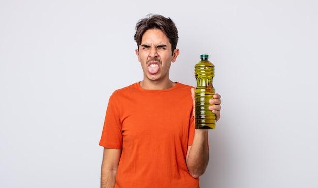 Jovem hispânico sentindo-se enojado e irritado e com a língua de fora. conceito de azeite
