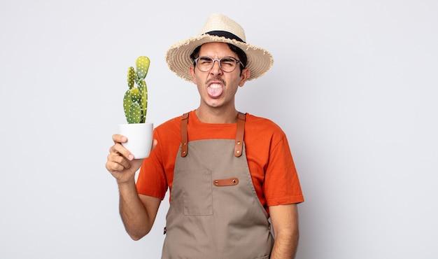 Jovem hispânico sentindo-se enojado e irritado e com a língua de fora. jardineiro com conceito de cacto