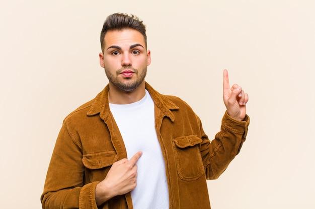 Jovem hispânico, sentindo-se orgulhoso e surpreso, apontando para si mesmo com confiança, sentindo-se como o número um bem-sucedido contra a parede isolada