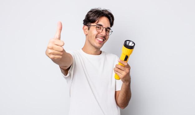 Jovem hispânico, sentindo-se orgulhoso, sorrindo positivamente com o polegar para cima. conceito de lanterna