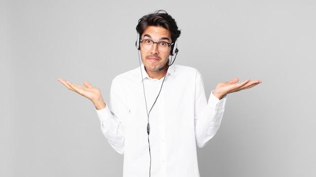 Jovem hispânico sentindo-se perplexo, confuso e em dúvida. conceito de telemarketing