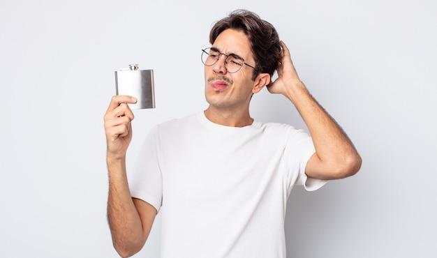 Jovem hispânico sentindo-se perplexo e confuso, coçando a cabeça. conceito de frasco de álcool