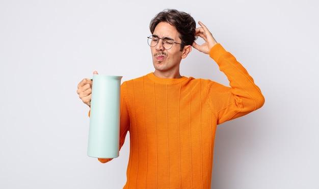 Jovem hispânico sentindo-se perplexo e confuso, coçando a cabeça. conceito de garrafa térmica
