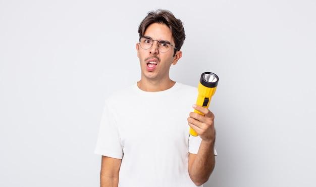 Jovem hispânico sentindo-se perplexo e confuso. conceito de lanterna