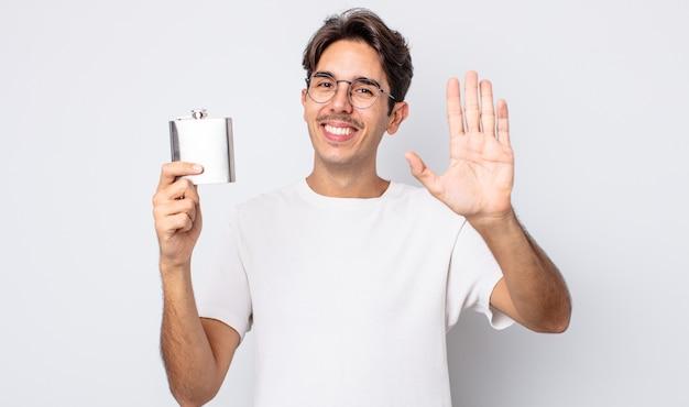 Jovem hispânico sorrindo alegremente, acenando com a mão, dando as boas-vindas e cumprimentando você. conceito de frasco de álcool