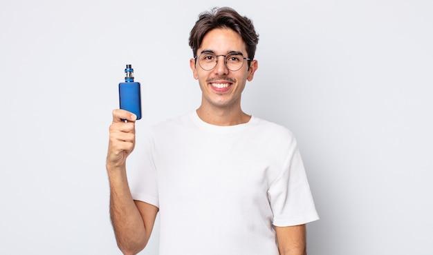 Jovem hispânico sorrindo alegremente com uma mão no quadril e confiante. conceito de vaporizador de fumaça