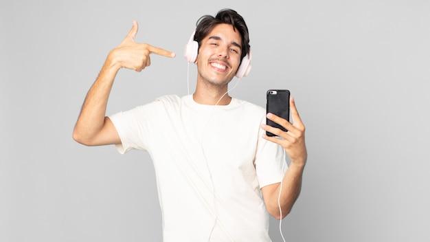 Jovem hispânico sorrindo com confiança apontando para o próprio sorriso largo com fones de ouvido e smartphone