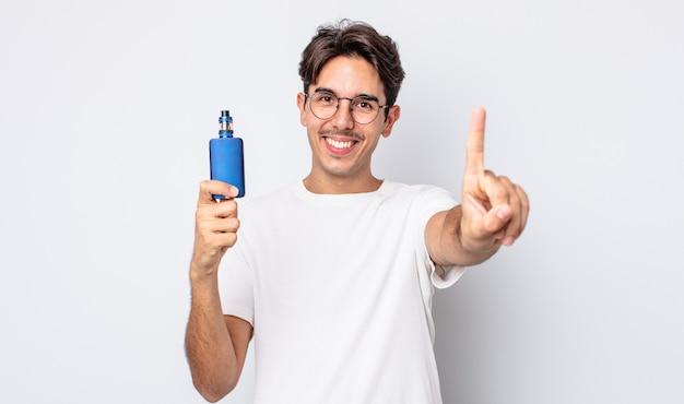 Jovem hispânico sorrindo com orgulho e confiança fazendo o número um. conceito de vaporizador de fumaça