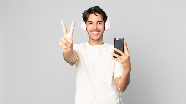 Jovem hispânico sorrindo e parecendo amigável, mostrando o número dois com fones de ouvido e smartphone