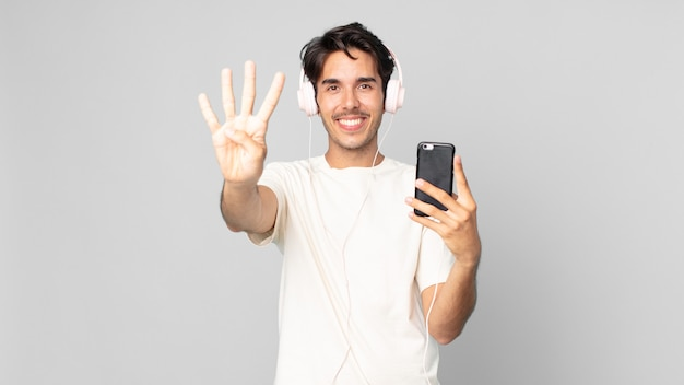 Jovem hispânico sorrindo e parecendo amigável, mostrando o número quatro com fones de ouvido e smartphone
