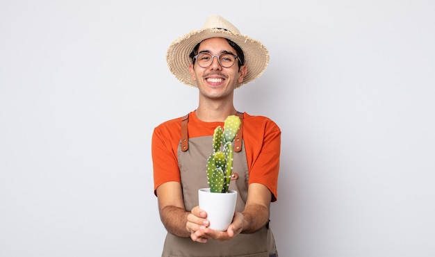 Jovem hispânico sorrindo feliz com amigável e oferecendo e mostrando um conceito. jardineiro com conceito de cacto