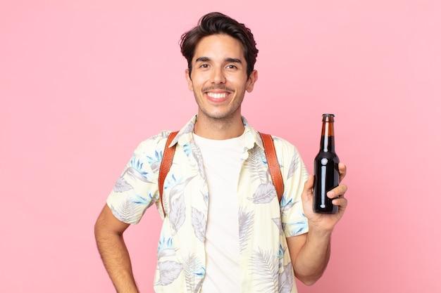 Jovem hispânico sorrindo feliz com uma mão no quadril e confiante, segurando uma garrafa de cerveja