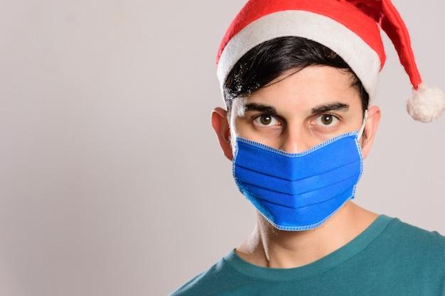 Jovem hispânico usando uma máscara facial e um chapéu de papai noel em fundo branco