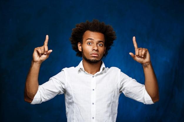 Jovem homem africano bonito apontando dedos acima sobre parede azul.