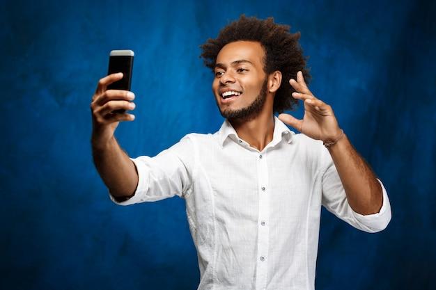 Jovem homem africano bonito fazendo selfie muro azul.