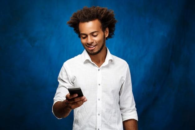 Jovem homem africano bonito olhando para celular por cima da parede azul.