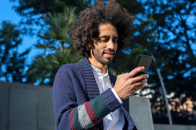 Jovem homem africano bonito usando seu smartphone com sorriso enquanto está sentado em um banco ao ar livre em dia de sol