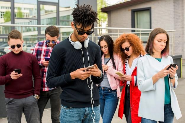 Jovem, homem africano, ficar, frente, amigos, usando, telefones móveis