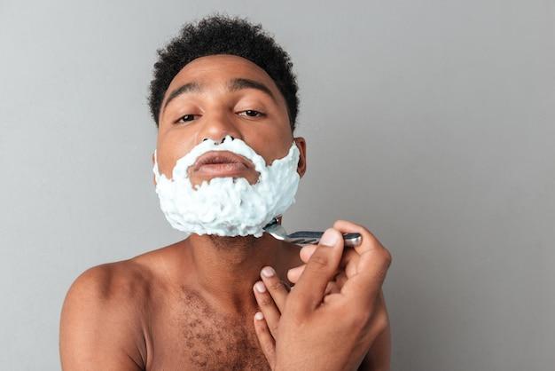Jovem homem africano nu barbear com uma navalha
