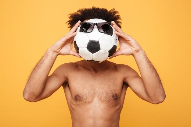 Jovem homem africano sem camisa, cobrindo a cabeça com uma bola de pé